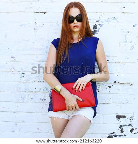 Young fashionable trendy girl posing  in white jeans, blue blouse and sunglasses holding handbag near white wall - stock photo