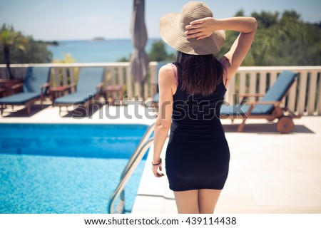 Young fashionable woman enjoying her vacation in villa beside the pool.Summer vacation,seaside villa house.Luxury lifestyle,successful woman on earned cruise.Europe summer holiday.Croatian island - stock photo