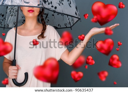 Young fashionable woman holding umbrella standing against grey background red hearts are floating around her. Love rain on Saint Valentine`s Day concept - stock photo