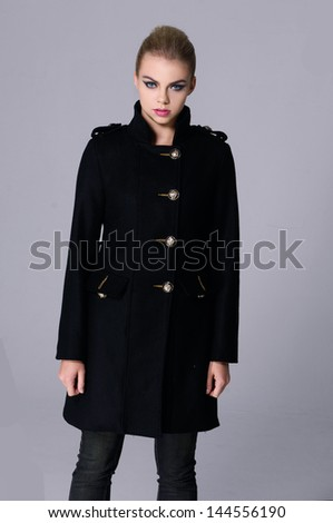 Young fashionable woman in black coat posing - stock photo