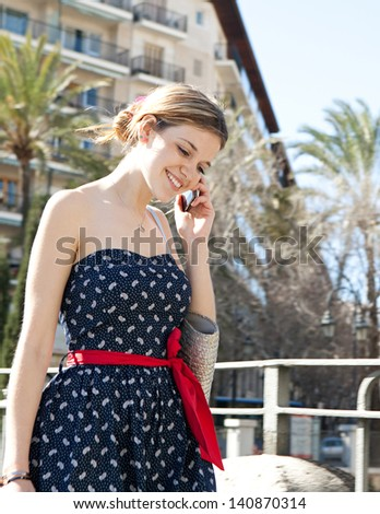 Young fashionable woman making a phone call using a smarphone while standing in a city bridge with railings, buildings and palm trees during a sunny day in the summer. - stock photo