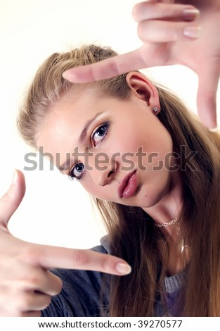 Young fashionable woman posing closeup making frame with her arms