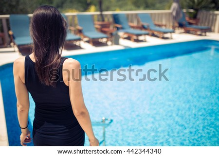 Young fashionable woman posing in a black dress while entering the pool.Beautiful sexy young woman with perfect slim figure with long dark hair. Girl enjoying her summer vacation. Luxury lifestyle. - stock photo