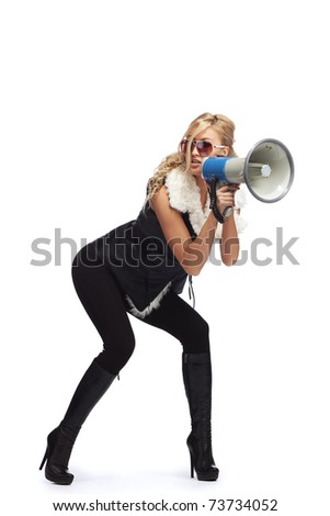 Young fashionable woman shouting in a megaphone - stock photo