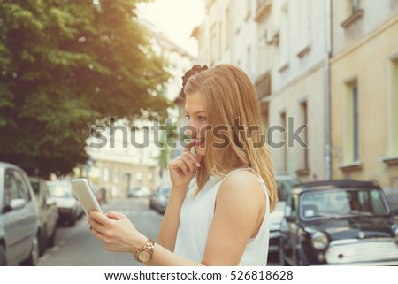 Young fashionable woman using cellphone outdoors.