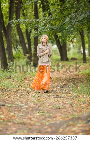 Young fashionable woman walking in spring park
