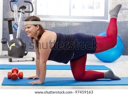 Young fat woman doing gymnastics at the gym, smiling. - stock photo