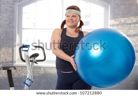 Young fat woman exercising with fit ball at the gym. - stock photo