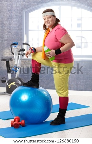 Young fat woman taking a break at the gym, resting leg on fit ball, drinking water. - stock photo