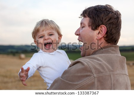 Young father and  adorable little son having fun on straw field, Germany.