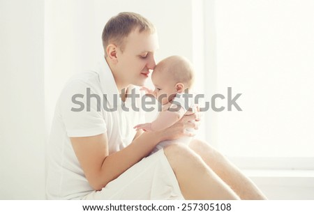 Young father and baby at home in white room sitting near window - stock photo