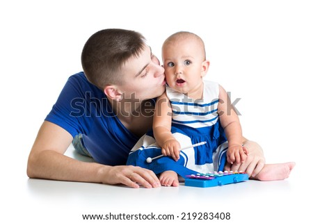 Young father and baby girl having fun with musical toys. Isolated on white background - stock photo