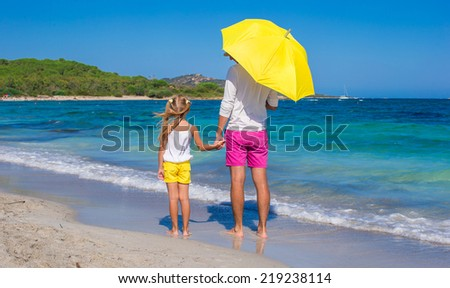 Young father and daughter at white beach with yellow umbrella - stock photo