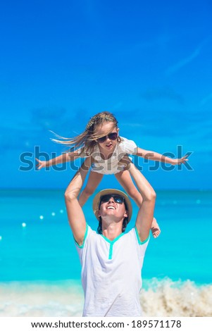 Young father and his adorable little daughter at tropical beach vacation - stock photo