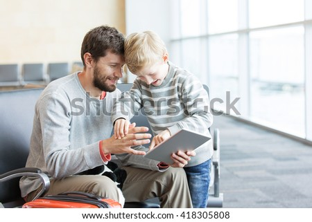 young father and his cheerful son waiting for departure at the airport and playing together at tablet computer, travel and vacation concept