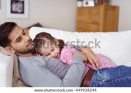 Young father and his cute little daughter taking a nap together on a sofa with the little girl lying on his chest - stock photo