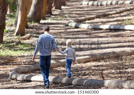 young father and his cute son walking and hiking in the woods - stock photo