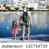 Young father and his daughter looking at the lake - stock photo