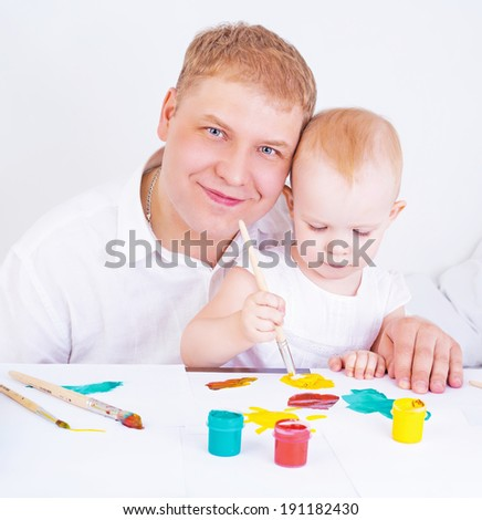 young father and his daughter painting at home - stock photo