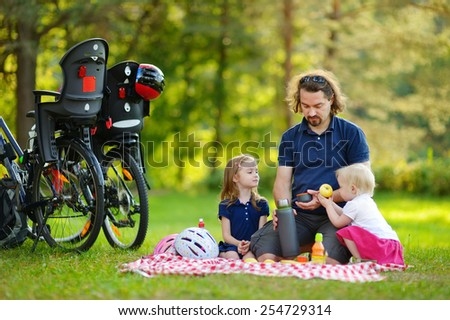 Young father and his daughters having a picnic in the park on beautiful summer day - stock photo