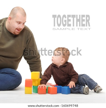 Young father and his kid playing with toy blocks on a white background.  - stock photo