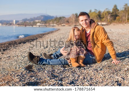 Young father and his little daughter at the beach on a sunny winter day - stock photo