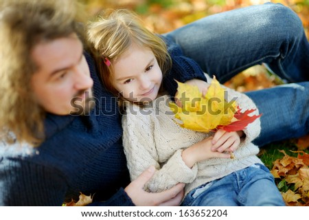 Young father and his little daughter have fun at autumn - stock photo