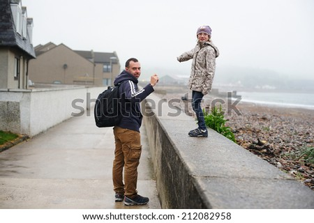 Young father and his little daughter on the beach in foggy, cool and rainy day.  - stock photo