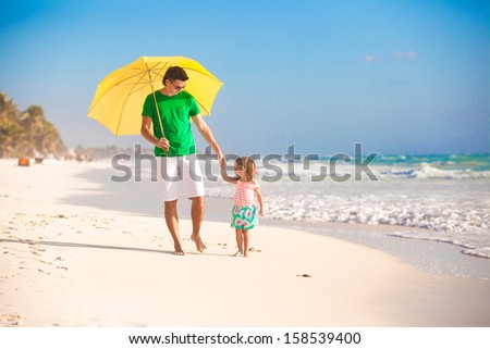 Young father and his little daughter walking under a yellow umbrella - stock photo