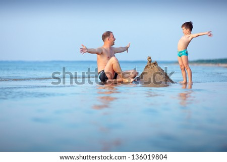 Young father and his little son building sand castle at beach - stock photo