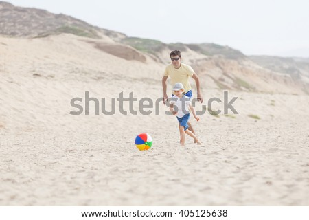 young father and his little son playing with ball at the beach, enjoying summer vacation - stock photo