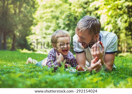 Young father and his son eating strawberries in Park. Picnic. Outdoor portrait - stock photo