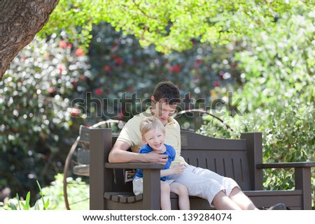 young father and his son sitting and having fun; family of two enjoying time together at summer - stock photo