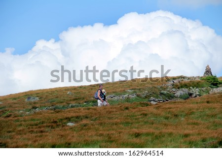Young father and his toddler daughter walking at the mountain meadow  - stock photo