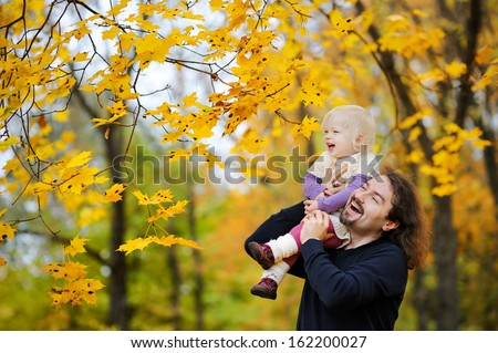 Young father and his toddler girl have fun at autumn