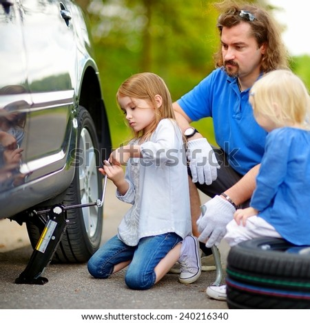 Young father and his two daughters changing a car wheel outdoors on beautiful summer day - stock photo