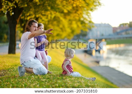 Young father and his two little daughters sitting by a river and watching canoes passing by - stock photo