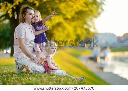 Young father and his two little daughters sitting by a river and watching canoes passing by