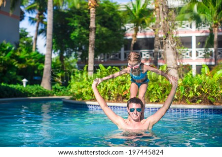 Young father and little adorable girl have fun in the pool - stock photo
