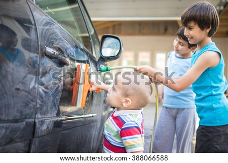 Young father and little boys washing car in summer day - stock photo