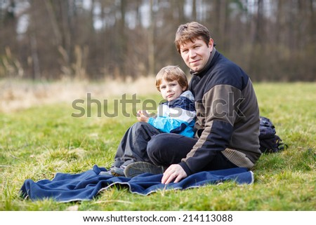 Young father and little son having picnic and fun near forest lake, nature on cold spring or autumn day.