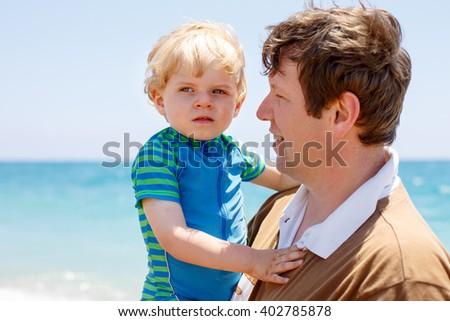 Young father and little toddler boy having fun on beach of ocean. man and kid son hugging. Carefree childhood and happy parenting. - stock photo