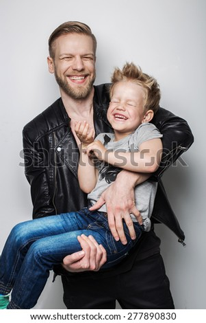 Young father and son laughing together. Fathers day.  Studio portrait over white background - stock photo