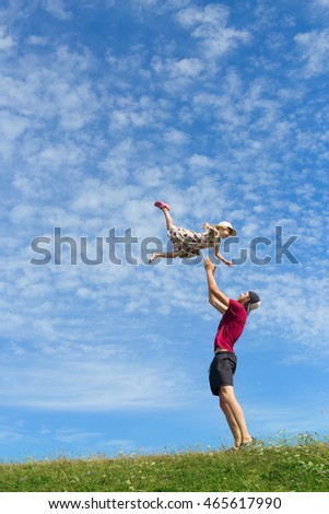 young father catching his daughter with arms in playful game, girl flying high in air outdoors with green grass and blue sky on background