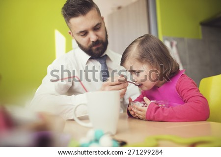 Young father feeding his little daughter