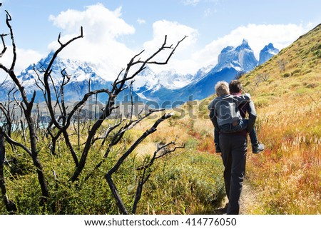 young father giving his son a piggyback ride during active and strenuous hike to mirador condor at torres del paine national park, patagonia, chile - stock photo