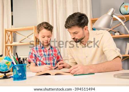 Young father helping his little son with homework