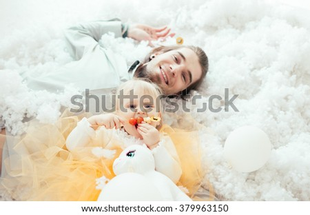 young father & his little daughter lie in fluff. girl in the classical tutu of golden tulle - stock photo