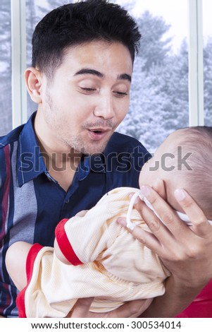 Young father holding and entertain male infant near the window at home - stock photo