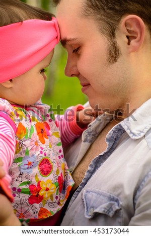 Young father holding his baby daughter - stock photo